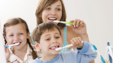 Mother and children brushing teeth